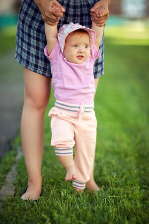 Mother teaching her baby to take the first steps barefoot on grass