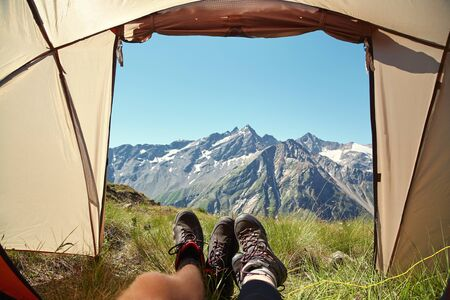 Two pairs of legs in hiking tourist boots at exit of tent