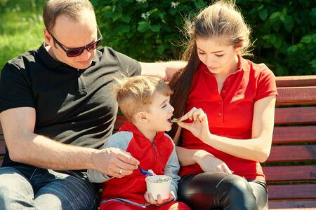 outdoor portrait of a happy family. Mom, dad and child eating ice cream. 写真素材