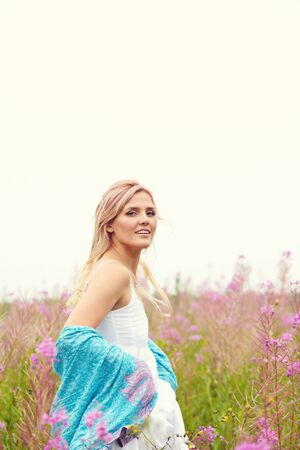 outdoor portrait of a middle aged blonde woman. attractive sexy girl in a field with flowers