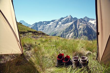 Two pairs of hiking tourist boots at exit of a tent 写真素材