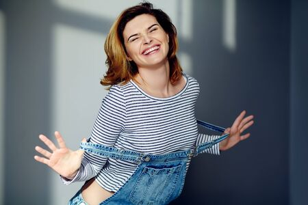 portrait of a young attractive stylish emotional smiling woman in jeans overalls. Foto de archivo