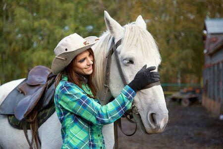 linda vaquera sonriente con un caballo blanco.