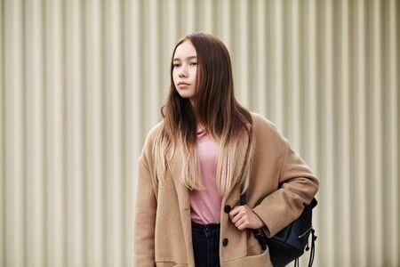 portrait en plein air d'une femme élégante dans une rue. Une fille moderne et élégante dans un manteau en cachemire beige tient un sac à dos noir Banque d'images