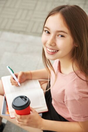 school girl writing pen in notebook on the knees. Student with coffee in a paper cup near university. Stok Fotoğraf