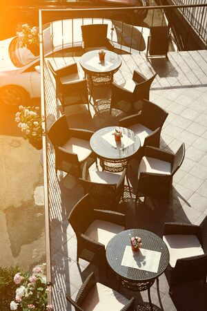 Cafe terrace with empty tables and chairs