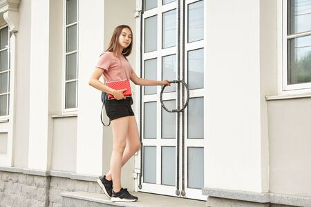 school girl with backpack and educational equipment. Student opening doors of the university. Reklamní fotografie