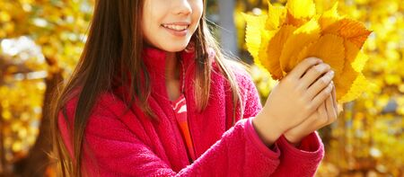 closeup beautiful smiling teenage girl with yellow leaves in autumn.