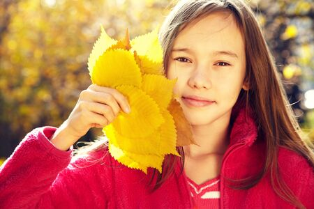 closeup portrait of a beautiful smiling teenage girl with yellow leaves in autumn.