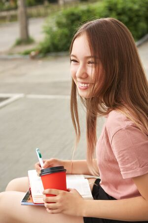 school girl writing pen in notebook on the knees. Student with coffee in a paper cup near university. Stok Fotoğraf - 129481689