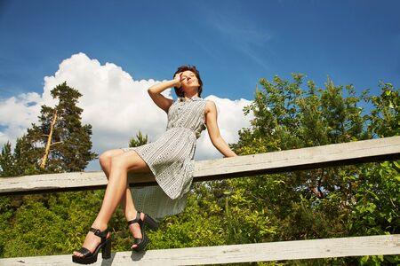 summer relax rustic portrait of a young woman sitting on fence in countryside.