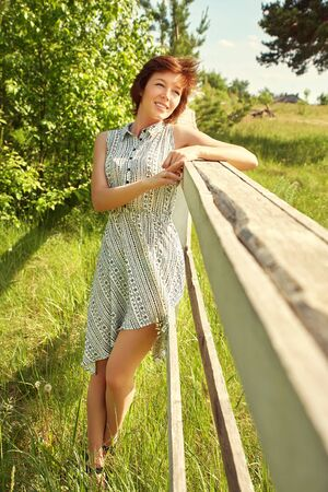 summer relax rustic portrait of a young woman near fence in countryside. Stockfoto