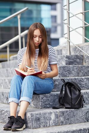 school girl writing in notebook on the knees. Student near university