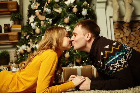 young couple celebrating Christmas at home. man and woman on New Year Eve.