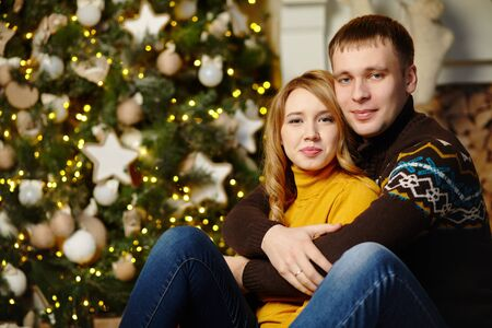 young couple celebrating Christmas at home. man and woman on New Year Eve