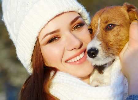 Jack Russell Terrier dog with owner woman in the winter outdoors.