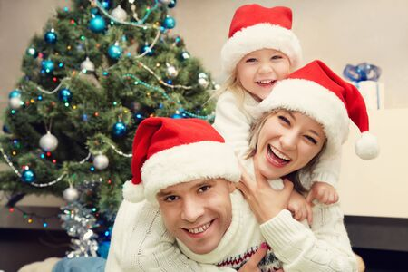 portrait of a young family. celebration at home. father, mother and child on the background of the Christmas tree. New Year and xmas people.