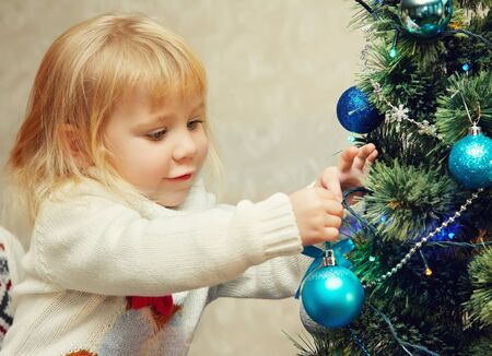little girl decorating a Christmas tree with blue balls. Stockfoto