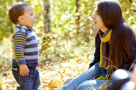 walking and playing young mother with her baby outdoors. Mom and son in an autumn park. Stockfoto