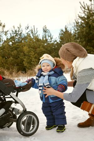 happy mother and baby in winter. family outdoors. cheerful mommy with her child.