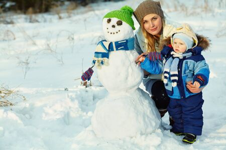 mother and baby in winter park. family outdoors. cheerful mommy with her child with snowman