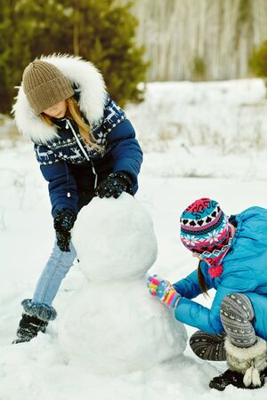 friends building a snowman. funny girls on a walk in the winter outdoors