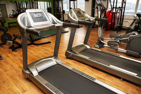 Treadmill in a gym. Fitness club equipment. Sports background
