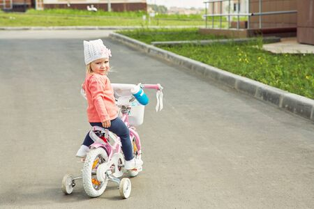 little girl riding a bicycle. child outdoor. Standard-Bild