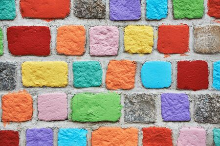 Stone multicolored wall. Brick painted background in colors of the rainbow Stock Photo