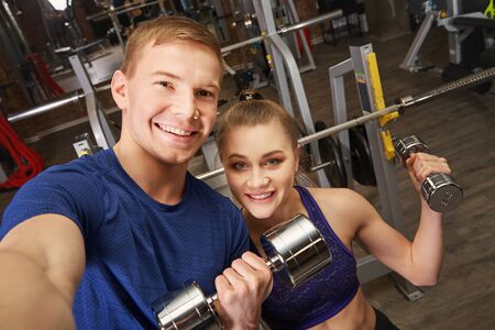 sport fit couple at gym. athletic young man and woman taking selfie photo. 版權商用圖片