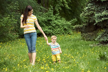 outdoor portrait of a mother with her child. Mom and son walking in a summer park on the grass with yellow dandelions.