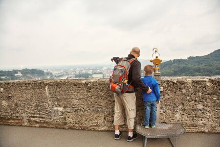 Father and son admire a city from an observation deck. Family sightseeing