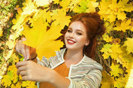 woman with yellow maple leaves in autumn