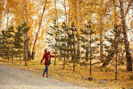 woman with yellow leaves in autumn park.