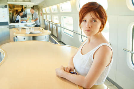 woman riding by train at the dining-car table. traveler on the road.