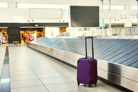 suitcase standing near empty conveyor belt at baggage claim at airport. Standard-Bild