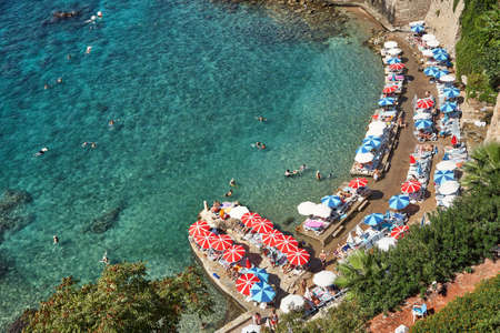 sea beach with people on vacation in sun loungers and sun umbrellas near the water. Standard-Bild