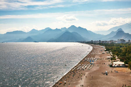 sea beach with people on vacation in sun loungers and sun umbrellas near the water and mountains.