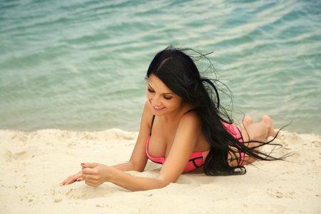 young beautiful sexy girl in swimwear lying on a sandy beach.