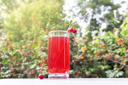 Cherry drink outdoors. Fruit drink from cherries in a glass.