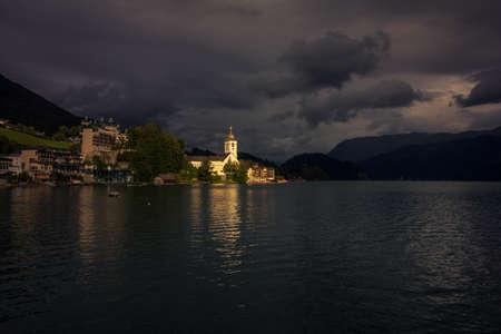 Sunlight shine on a church in popular travel destination of Lake Wolfgang (Wolfgangsee) in Salzburg, Austria