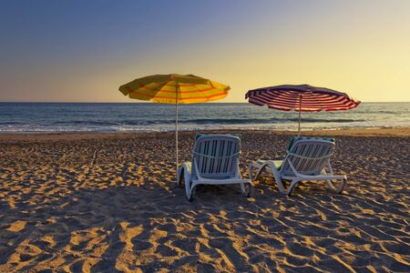 Two empty chairs under sun shades on a sandy beach in summer time Stock Photo