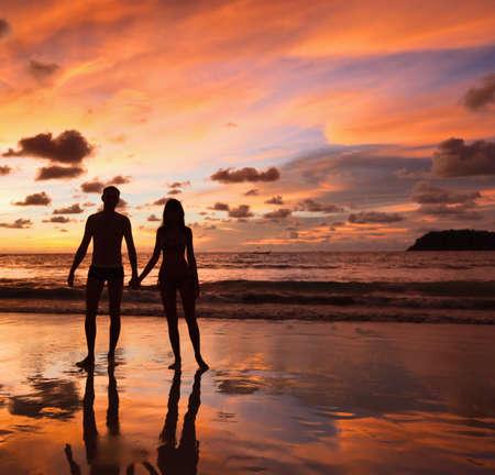 Silhouetten der Liebhaber auf einem Hintergrund eines Sonnenuntergangs