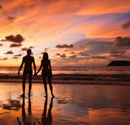 Silhouettes of lovers on a background of a sunset photo