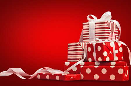 Weihnachtsgeschenke mit Band auf einem roten Hintergrund Standard-Bild