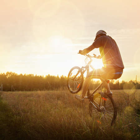 Sportsman riding a bike at sunset. Sport lifestyle photo