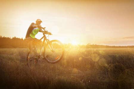 Sportsman riding a bike at sunset. Sport lifestyle Stock Photo - 27240792