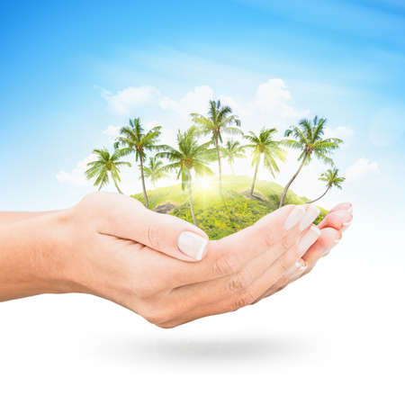 Tropical island with palm trees, blue sky and clouds at the open hands photo