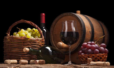 Still life with wine bottles, glasses and oak barrels isolated on black photo