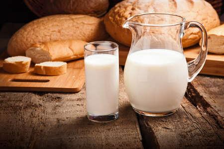 Kruik met melk close-up op de achtergrond brood
